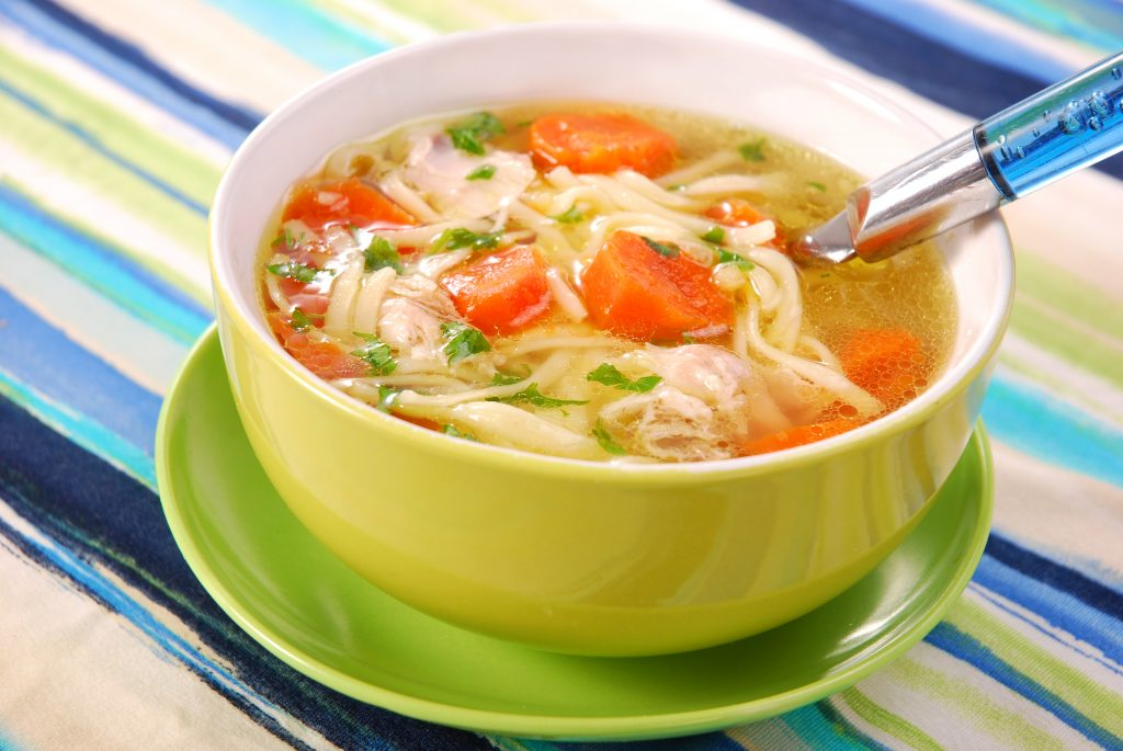 Bowl of clear chicken soup with noodle and vegetables