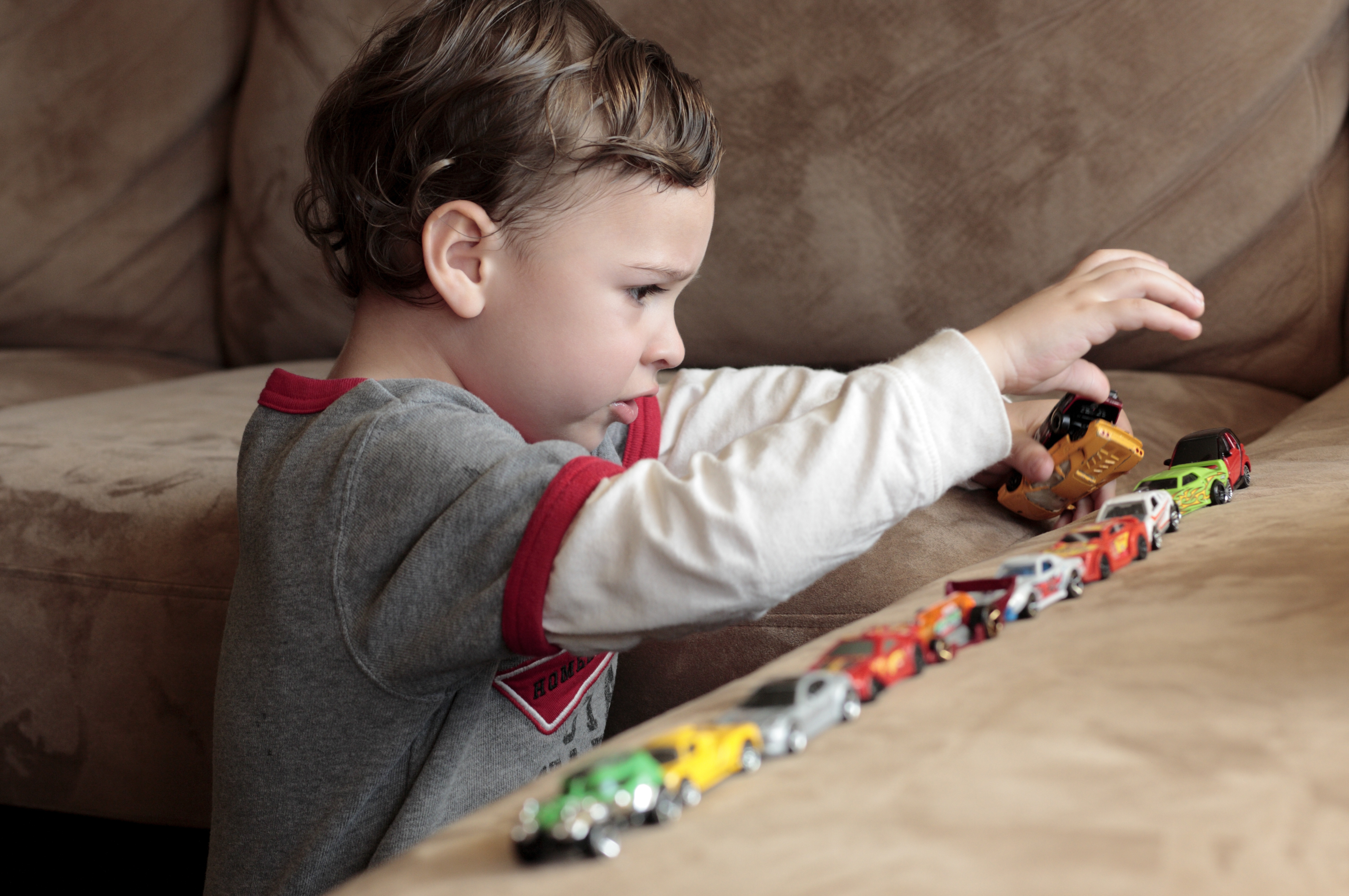 Autistic boy playing with toy cars
