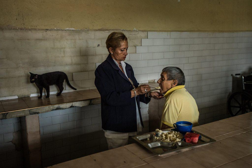 سرپرستار، بیمار نابینا و گربۀ قصۀ ما. © Meridith Kohut for The New York Times