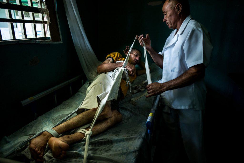 رائول حملۀ عصبی حادی را تجربه میکند. به همین دلیل او را به تخت میبندند. © Meridith Kohut for The New York Times