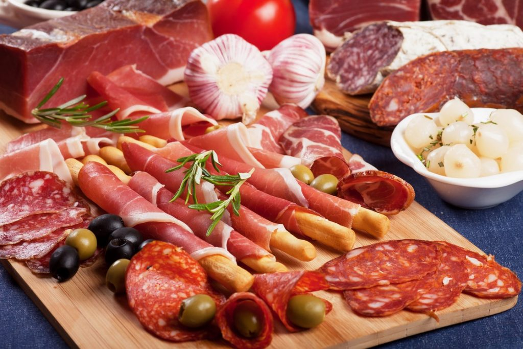 Sliced prosciutto di Parma on wooden board with olives and rosem