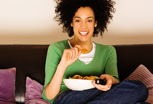 thinkstock_rf_photo_of_woman_snacking_watching_tv