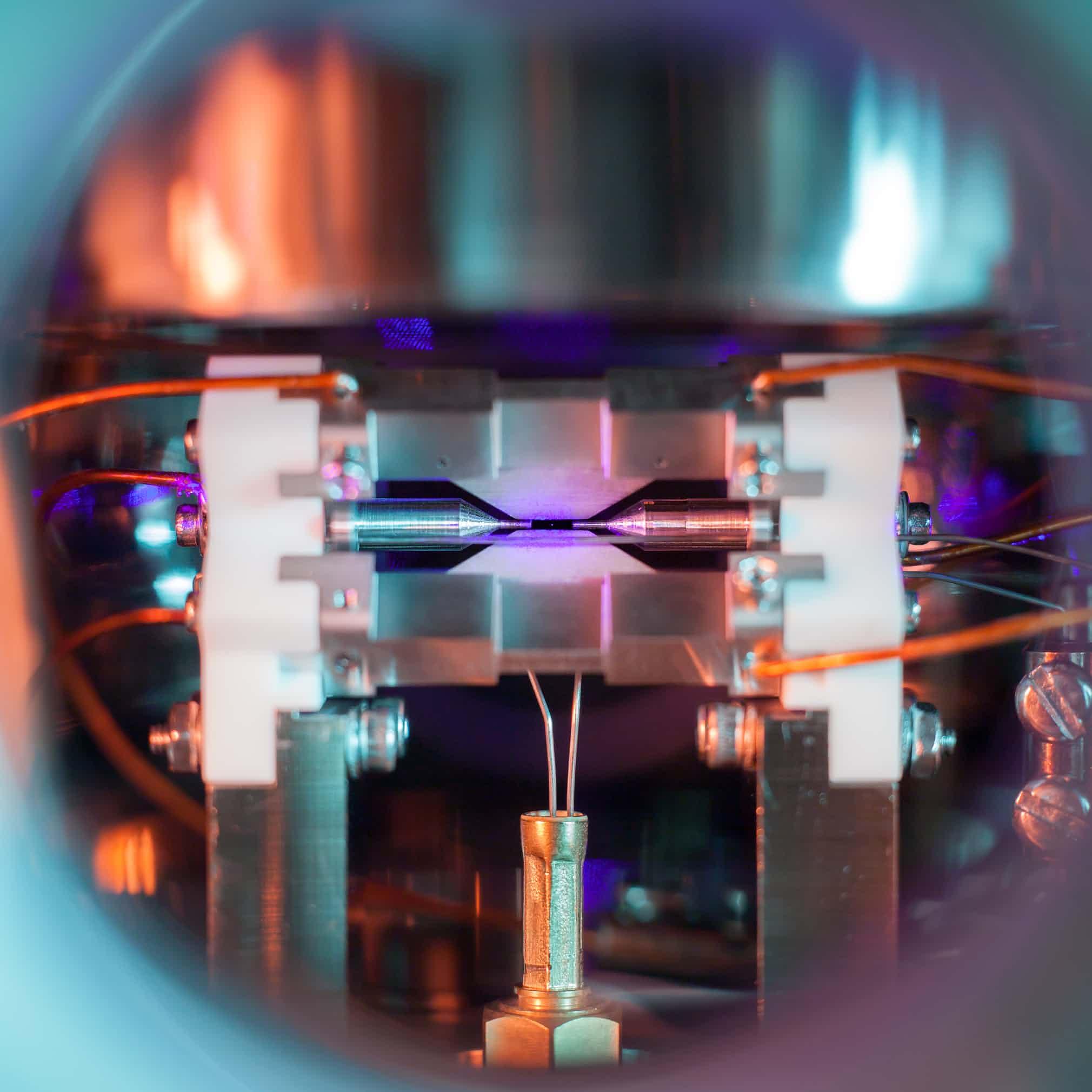 اتم منفرد در تلهی یونی. David Nadlinger از دانشگاه آکسفورد. در مرکز تصویر، یک نقطهی روشن و بسیار ریز میبینید: یک اتم استرانتیوم با بار مثبت. این اتم به دلیل وجود میدانهای الکتریکی اطرافش، تقریباً بدون حرکت نگه داشته شده است.